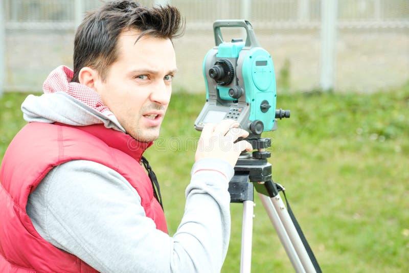 土木工程师土地调查用tacheometer或经纬仪设备 检查路的工作者建造场所 免版税库存照片