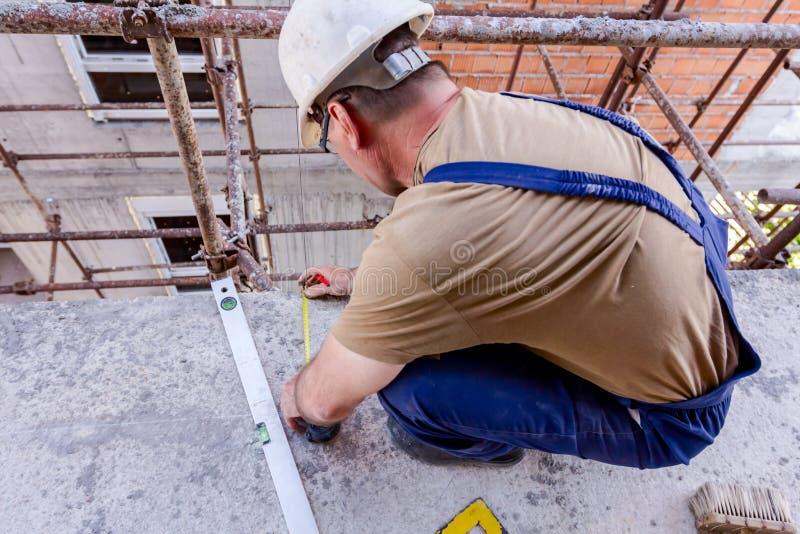 土木工程师在建筑工地标记与铅笔的点在混凝土 库存照片