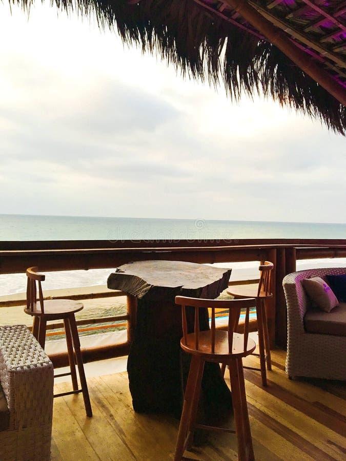 土气俯视海洋的酒吧表和椅子 库存照片
