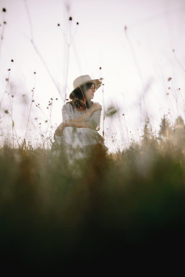 土气坐在野花和草本中的礼服和帽子的时髦的女孩在山的晴朗的草甸 放松Boho的妇女  库存图片