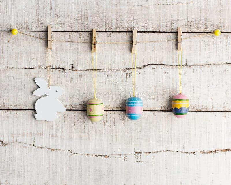 土气复活节背景:葡萄酒被绘的鸡蛋和白色兔宝宝在晒衣夹垂悬对老白色木墙壁 节假日概念 免版税库存图片