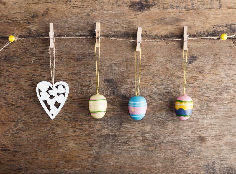 土气复活节背景:葡萄酒被绘的鸡蛋和白色心脏在晒衣夹垂悬对老棕色木墙壁 节假日概念 库存图片