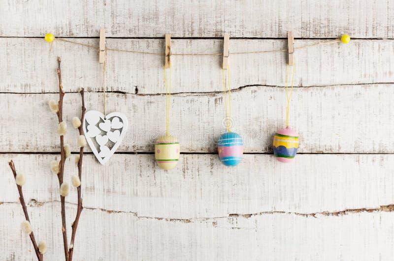土气复活节背景:葡萄酒被绘的鸡蛋和白色心脏在晒衣夹垂悬对老白色木墙壁 节假日概念 免版税库存照片