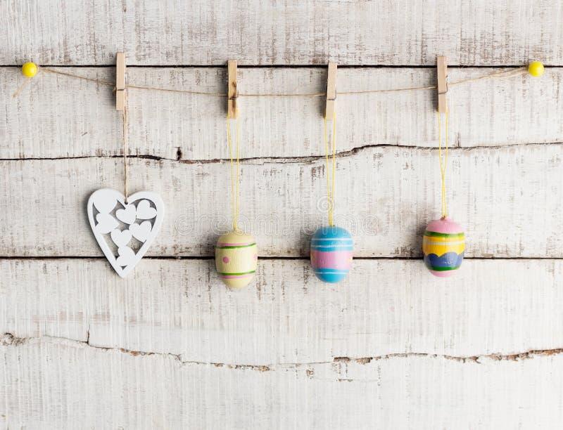 土气复活节背景:葡萄酒被绘的鸡蛋和白色心脏在晒衣夹垂悬对老白色木墙壁 免版税库存图片