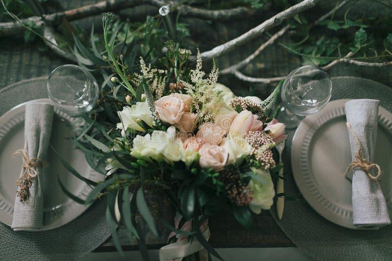 土气婚礼装饰 不同的花花束在装饰的桌上的两的 免版税图库摄影
