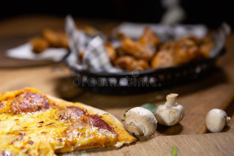 土气小餐馆客栈食物比萨和篮子鸡翅 免版税库存照片
