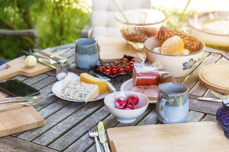 土气庭院桌为与家庭的外部膳食做准备 库存照片