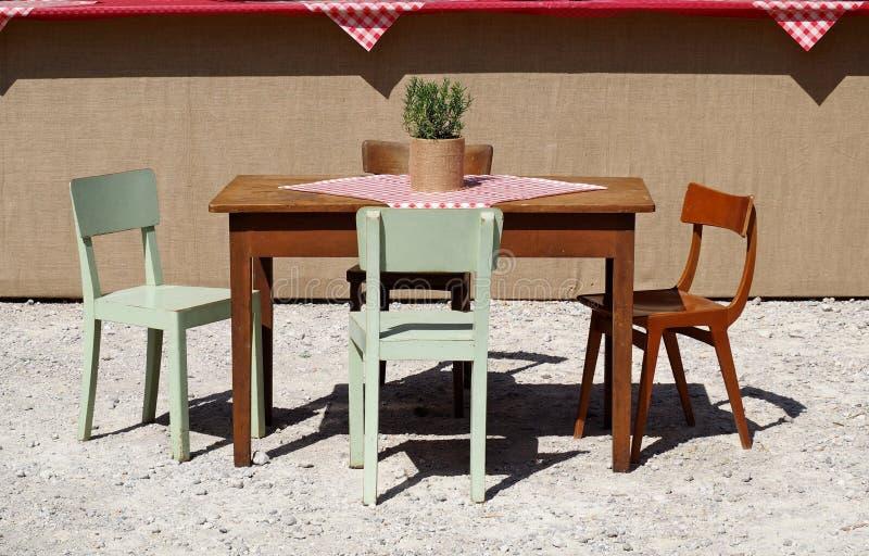 土气木桌和色的椅子,与方格的桌布和迷迭香植物,在一个石渣前院 免版税库存照片