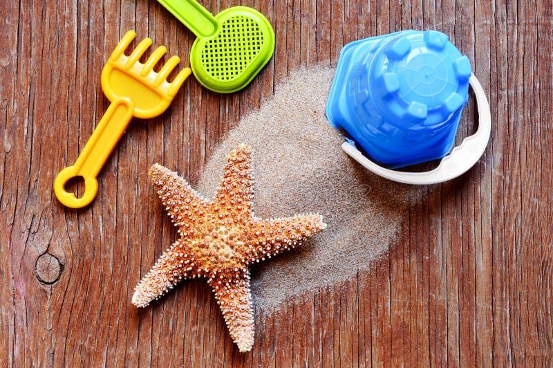土气木表面上的海星、沙子和海滩玩具 免版税库存图片