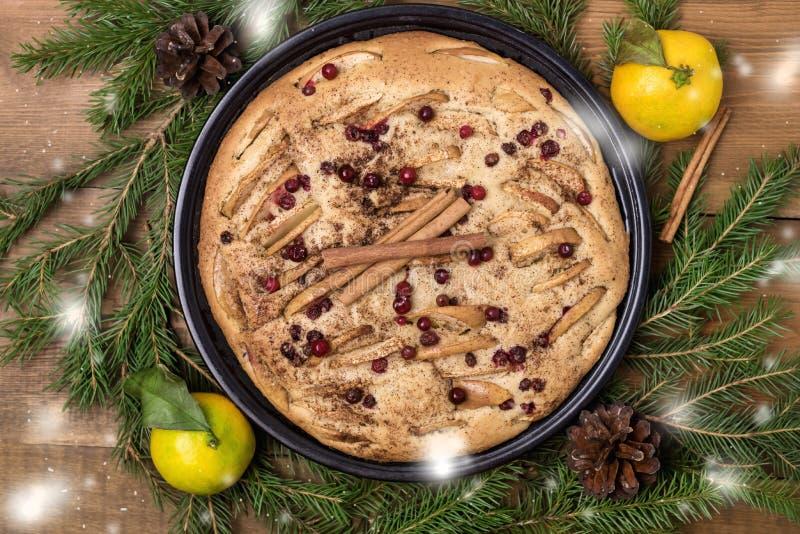 土气样式鲜美自创苹果计算机莓果蛋糕用香料冷杉分支柑橘木背景平的被放置的雪圣诞节食物Concep 免版税库存照片