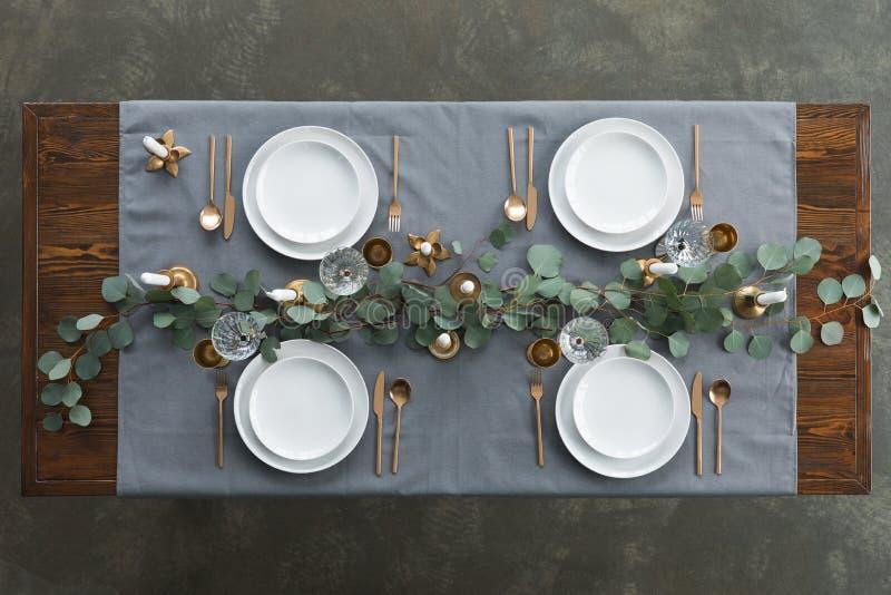 土气桌设置顶视图与玉树、失去光泽的利器、酒杯、蜡烛和空的板材的在桌面 免版税库存照片