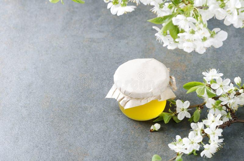 土气瓶子灰色老表面上的蜂蜜和bloosom花 您的设计的空的空间 库存照片