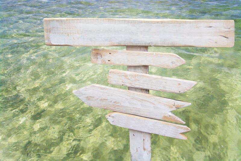 土气白色空被集中的木签署新鲜的绿色海洋水 免版税库存照片