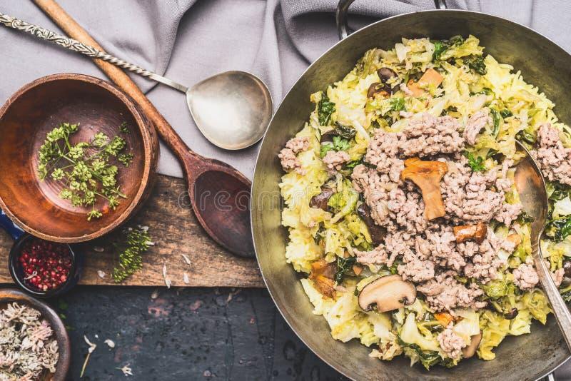 土气的食物 盘用被炖的百果馅、圆白菜、米和蘑菇与烹调匙子在黑暗的葡萄酒背景 免版税图库摄影