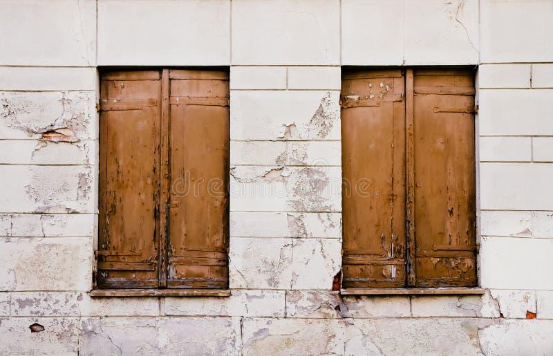 土气老脏和被风化的棕色木闭合的窗口关闭与在白色破裂的墙壁上的削皮油漆 库存照片