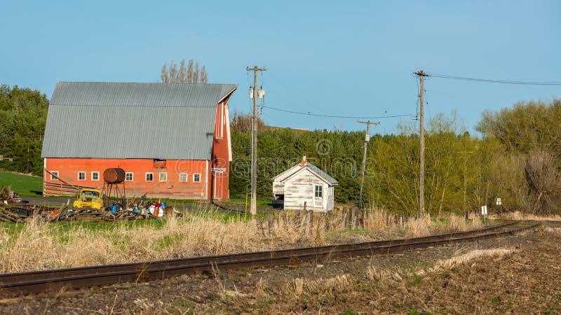 土气老谷仓和生锈的火车轨道 库存图片