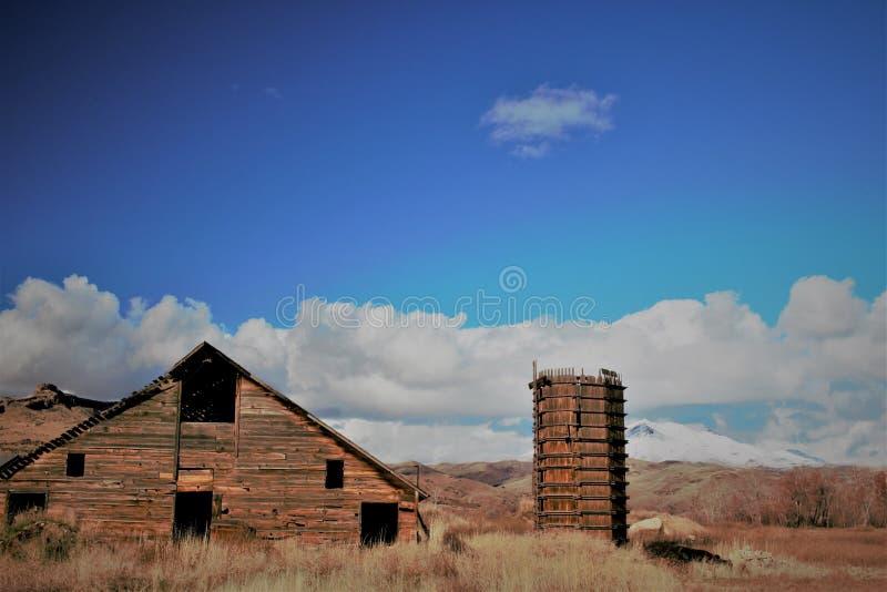 土气谷仓和水塔,雪加盖了山后面地面 库存图片