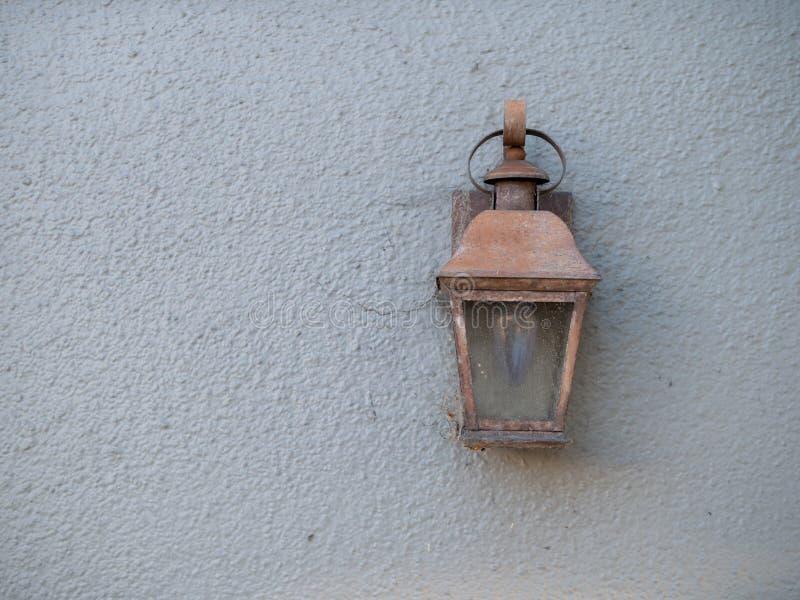 土气铜灯附有了在白色墙壁上的一个房子外 免版税库存照片