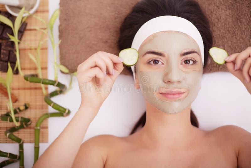 黏土泥面具的美丽的少妇在面孔覆盖物注视用切片黄瓜 库存照片