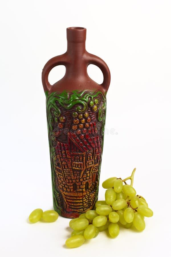 黏土瓶和葡萄 免版税库存图片