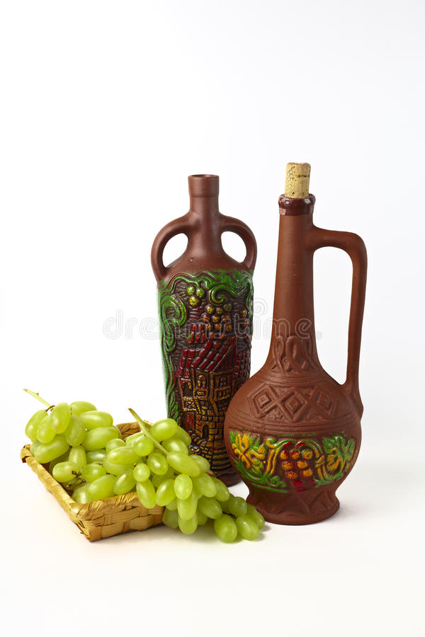 黏土瓶和葡萄 免版税库存照片