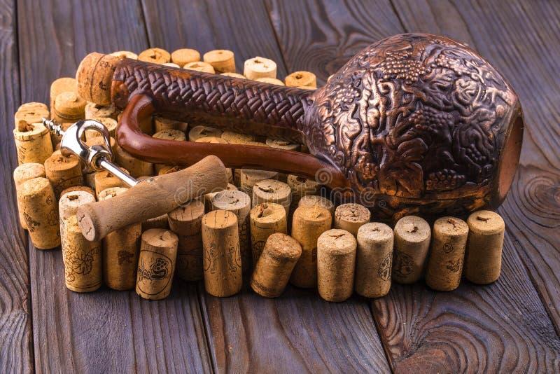 黏土瓶酒和黄柏与一个拔塞螺旋在一张木桌上 免版税图库摄影