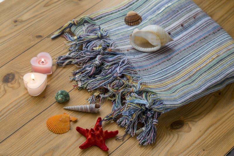 土耳其厚绒毛巾peshtemal与贝壳、海星和蜡烛 库存照片