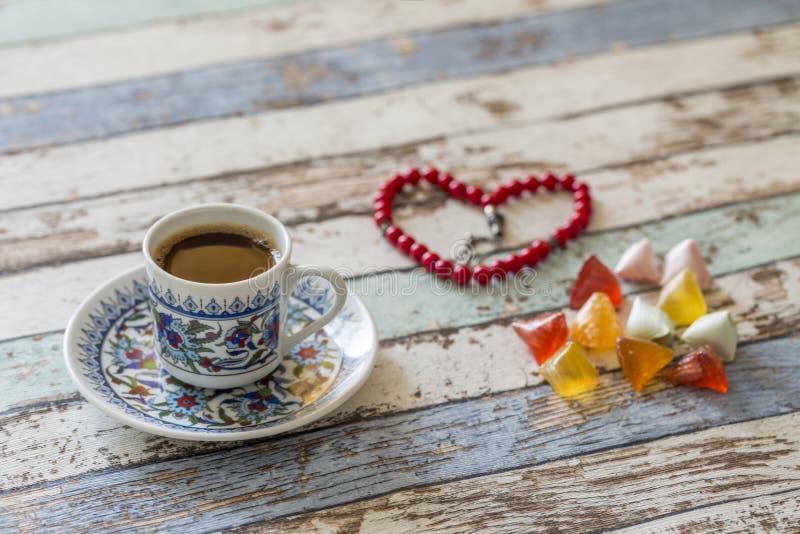 土耳其咖啡、冰糖和心形的念珠在桌上 免版税图库摄影