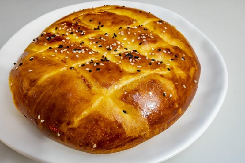土耳其斋月面包、皮塔饼面包在白色板材有sesames的和黑种子 免版税库存照片