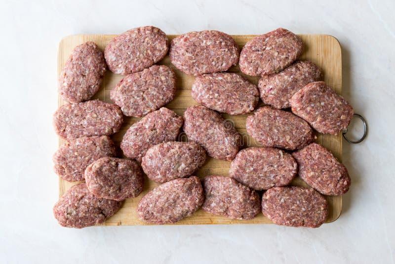 土耳其未加工的丸子Kofte或Kofta做用肉末在木表面 免版税库存图片