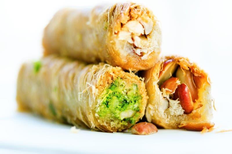 土耳其点心-果仁蜜酥饼用花生, pistachious,在白色背景的蜂蜜 健康甜点 复制空间 图库摄影