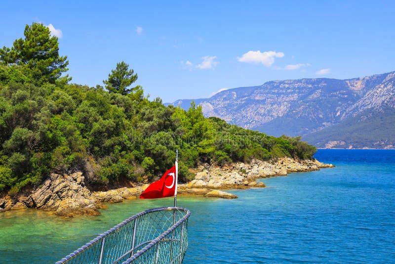 土耳其的旗子船的弓的以美丽如画的海岸和山为背景的 免版税库存图片