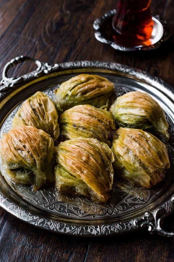 土耳其米蒂耶果仁蜜酥饼淡菜塑造与绿色开心果粉末、黄油奶油和传统茶的Baklawa在银色盘子 图库摄影