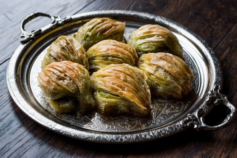 土耳其米蒂耶果仁蜜酥饼淡菜塑造与绿色开心果粉末和黄油奶油的Baklawa在银色盘子 免版税库存照片