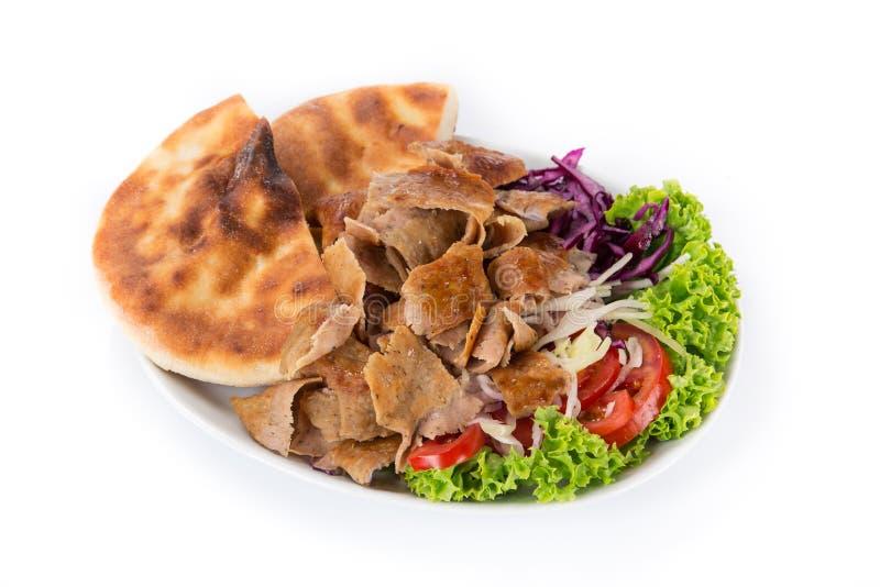 土耳其语在白色背景的Doner Kebab板材 库存图片