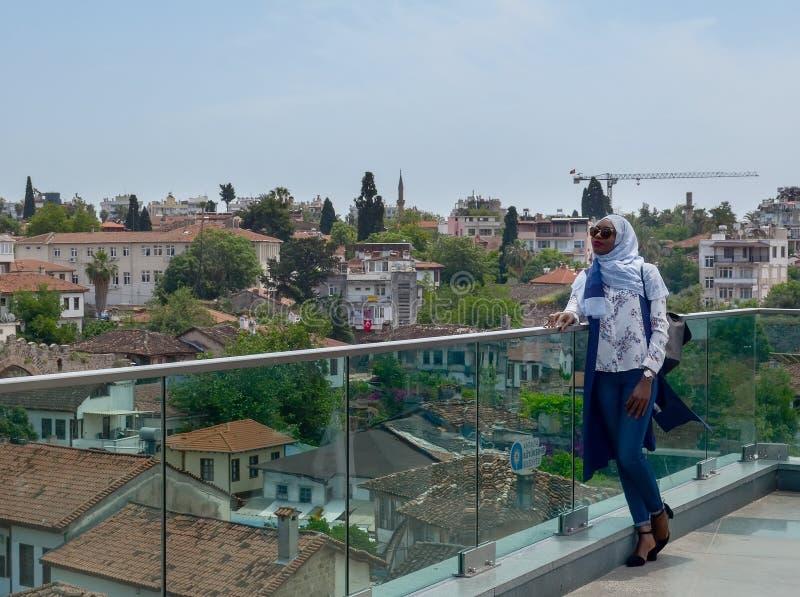 土耳其,安塔利亚, 2018年5月10日 美丽的衣裳、站立在观察平台的头巾和太阳镜的非洲少妇 免版税库存图片