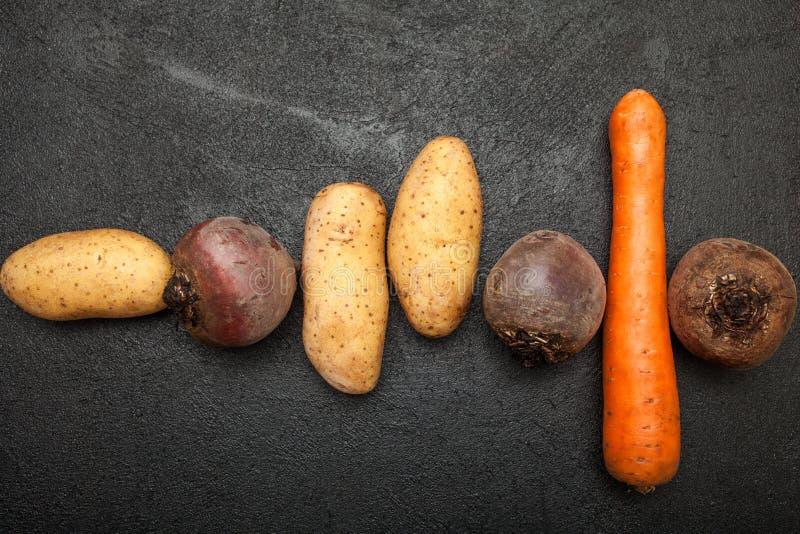土豆肿胀、甜菜和红萝卜在一张黑桌上 免版税图库摄影