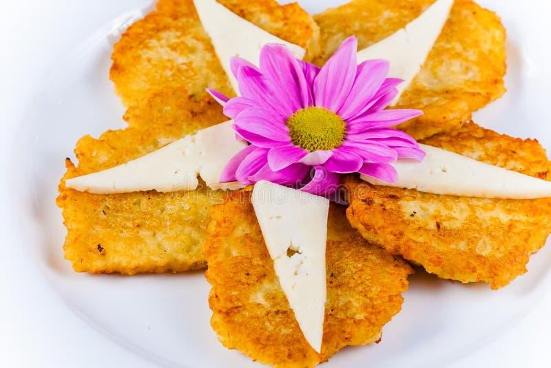 土豆薄烤饼用在白色板材的乳酪 库存照片