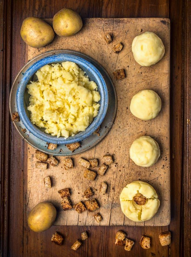 土豆饺子用油煎方型小面包片,在切板,德国国民食物的准备 免版税库存图片
