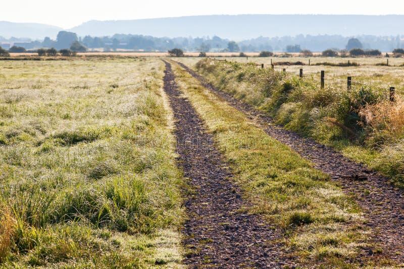 Download 土路在有露水的一个草甸 库存图片. 图片 包括有 天空, 地产, 农村, 乡下, 石渣, 农田, 肩膀, 国家(地区) - 59112071