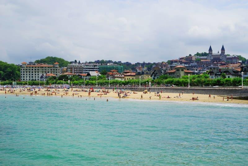 圣・萨巴斯蒂安,西班牙- 2018年7月24日:Playa de Ondarreta在一好日子 塞米纳里奥Diocesano de圣・萨巴斯蒂安背景权利 免版税库存照片