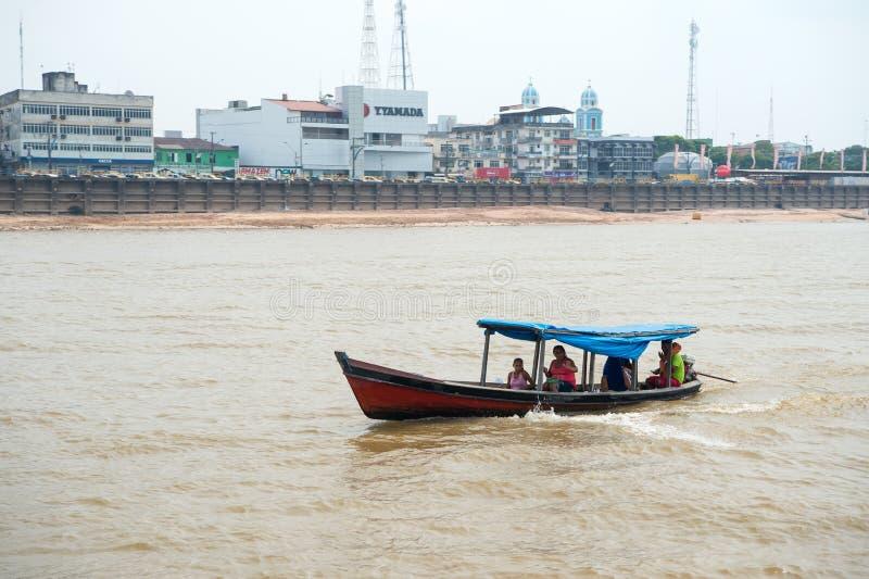 圣塔伦,巴西- 2015年12月02日:有人的小船亚马孙河的 沿河岸的汽艇浮游物有房子的 由wa的旅行 免版税库存照片