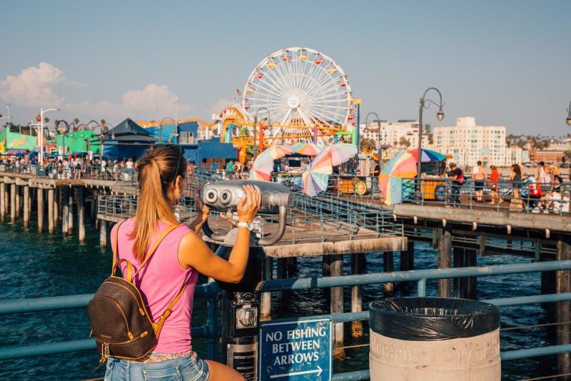 圣塔蒙尼卡码头的女孩观看的游乐园 库存照片