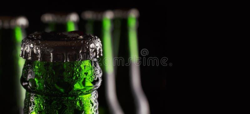 圣帕特里克` s日 在瓶的新鲜的绿色啤酒有凝析油下落的在黑背景的 概念:客栈,圣帕特里克` s天c 免版税图库摄影