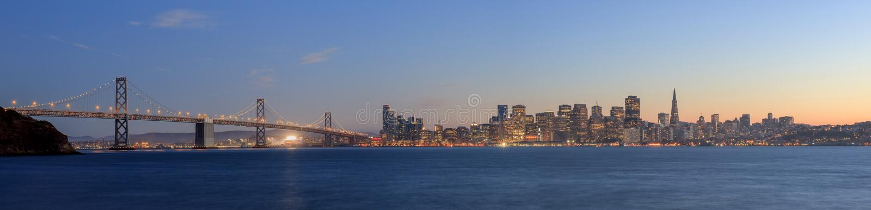 圣弗朗西斯科奥克兰有光的海湾桥梁在日落时间 免版税库存图片