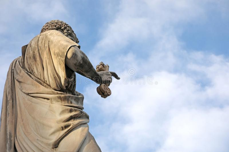 圣彼得古老雕象钥匙的在手和天空蔚蓝上 免版税库存照片