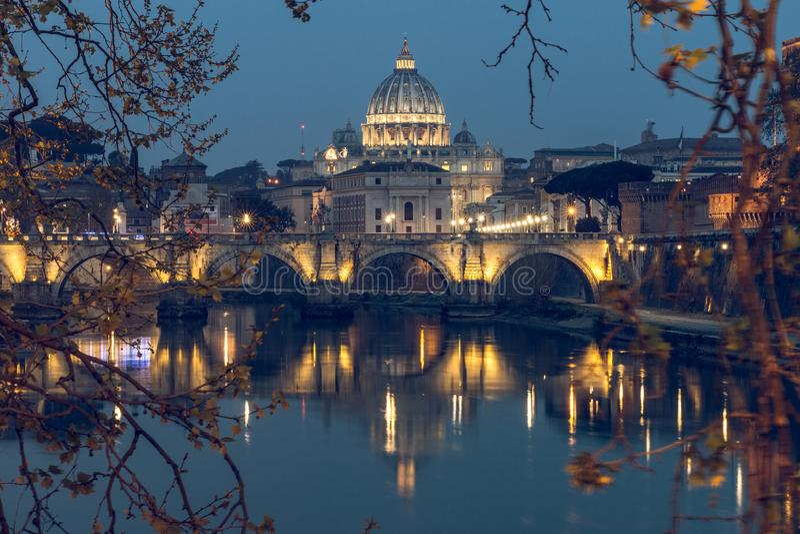圣彼得大教堂大教堂和台伯河有奥里略凯旋门桥梁的通过树看了在夜之前 免版税库存照片