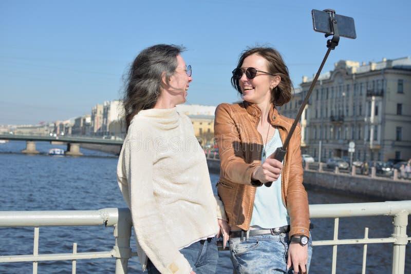 圣彼德堡俄罗斯作为selfies的少女游人在一个木桥在历史市中心 库存照片