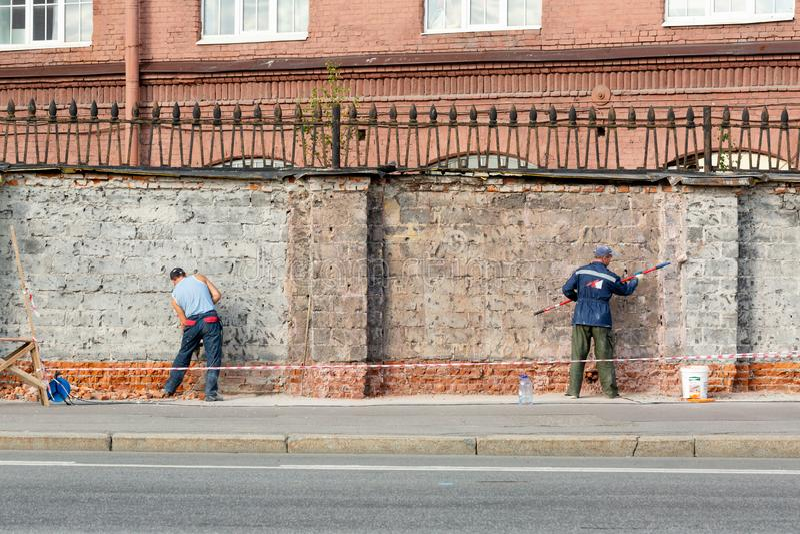圣彼德堡,俄国联盟8月16日2018年:修理砖篱芭的工作者 免版税图库摄影