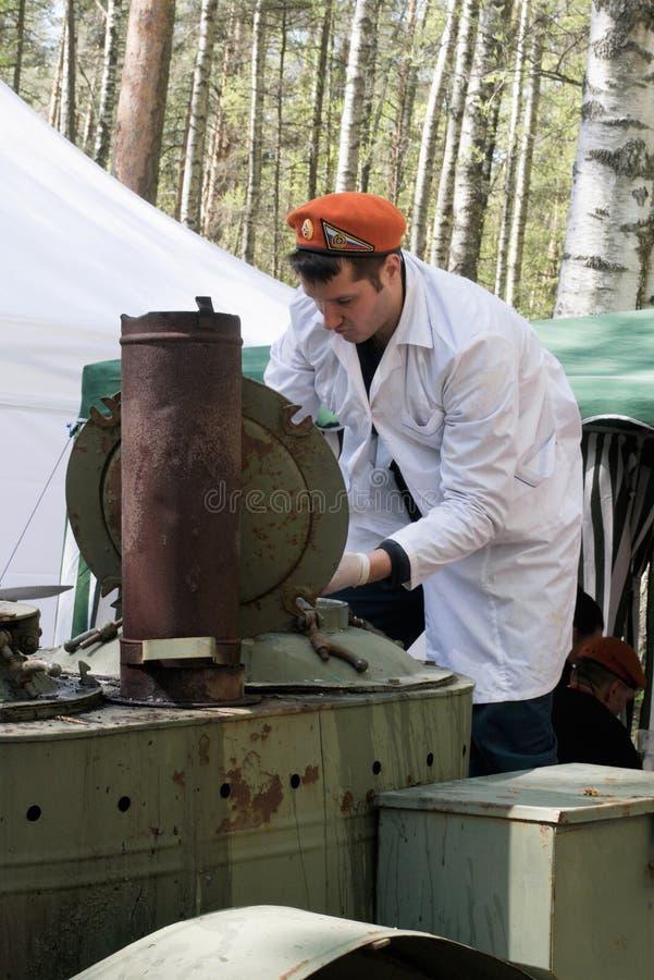 圣彼德堡,俄罗斯,2019年5月 烹调粥的军事厨师在野外用的全套炊具里在公园 免版税库存照片